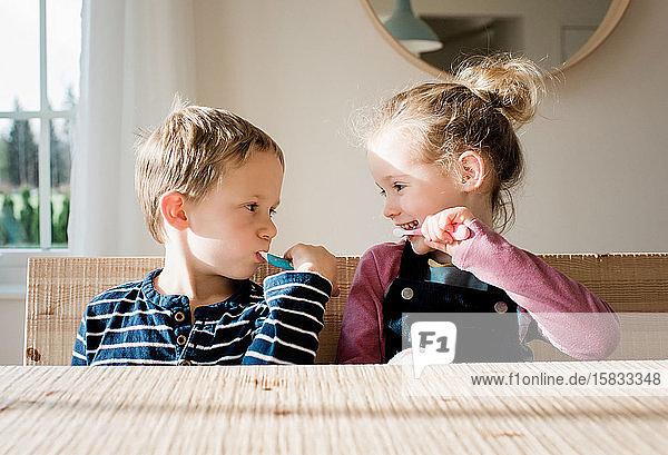 Geschwister putzen sich zu Hause vor der Schule die Zähne