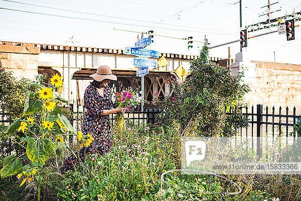 glückliche Frau im Stadtgarten mit frischen Blumen
