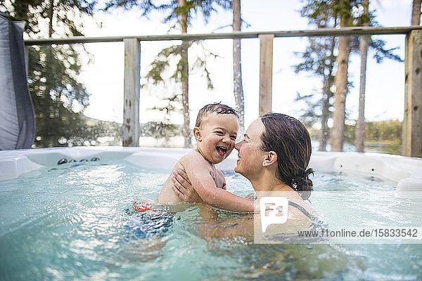 Junge spritzt und spielt mit der Mutter im Schwimmbad