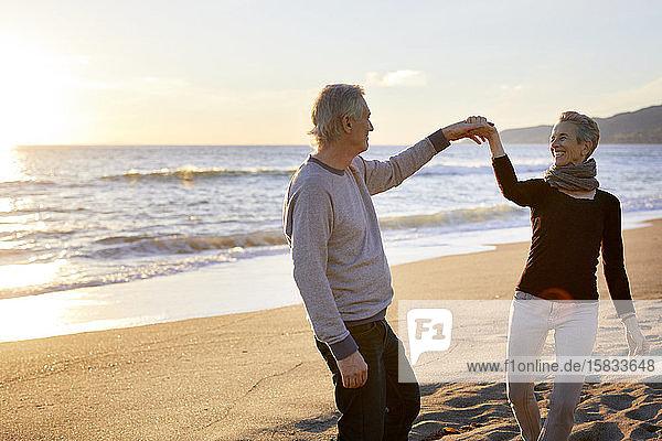 Lächelndes älteres Paar tanzt bei Sonnenuntergang am Strand