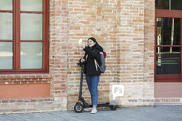 junge Frau  die Roller fährt und ein Selfie