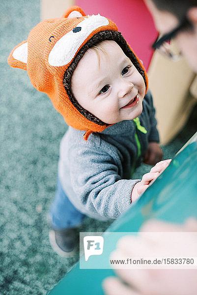 Kleiner Junge mit Fuchshut auf dem Spielplatz  der seinen Vater anlächelt.