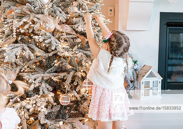 Toddler in pink dress putting an ornament on a flocked christmas tree