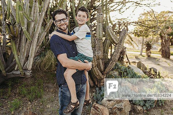 Porträt eines Vaters  der einen älteren Sohn hält und in die Kamera lächelt