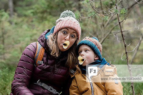 Mutter und Sohn machen beim Wandern im Winter beim Essen alberne Gesichter