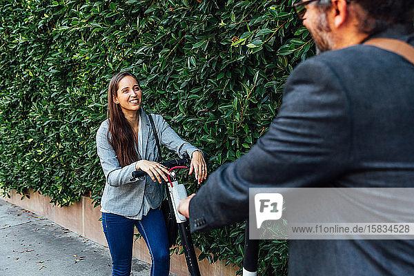 Frau lächelt Mann mit Roller an