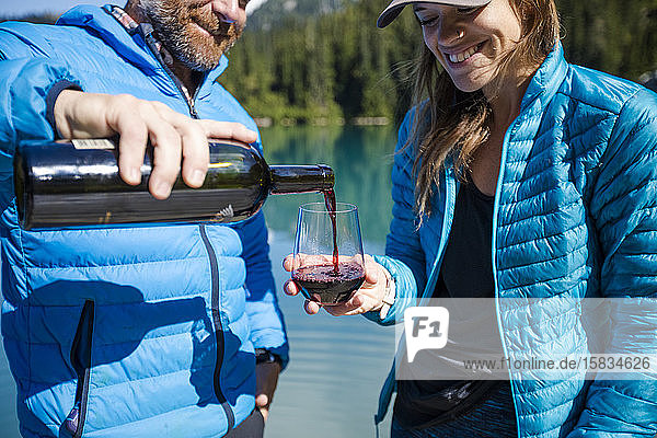 Man pours glass of wine for his partner at the lake.