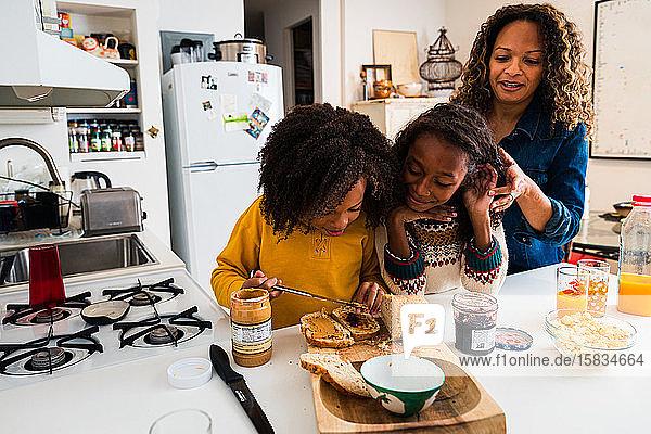 Mother tying hair of daughter looking at sister preparing breakfast in kitchen