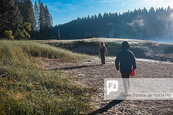 Zwei Kinder spazieren auf einer Wiese in der Nähe eines nebligen Sees im Sly Park