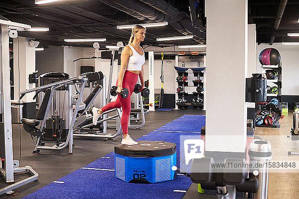 Eine blonde Frau  die im Fitnessstudio trainiert.
