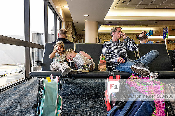 two girls and father sitting in airport terminal waiting for plane