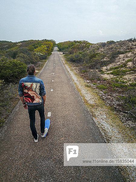 Ein Mann mit langen Haaren skatet auf einer leeren Straße in Europa