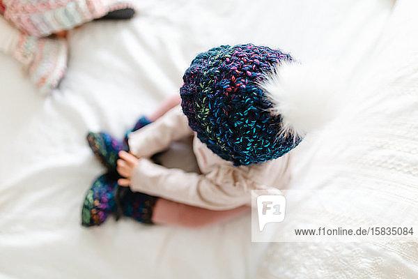 Kleinkind sitzt auf einem weißen Bett in einer Strickmütze mit weißem Bommel