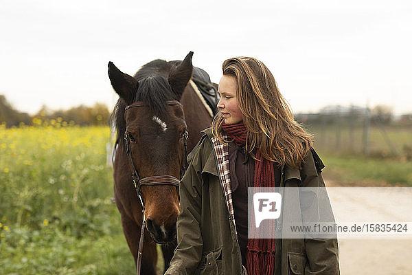 junge Frau mit einem Pferd auf einer Rennbahn