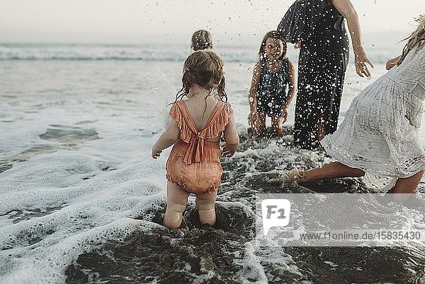 Junges Kleinkind planscht mit Schwestern und Mutter am Strand in der Abenddämmerung