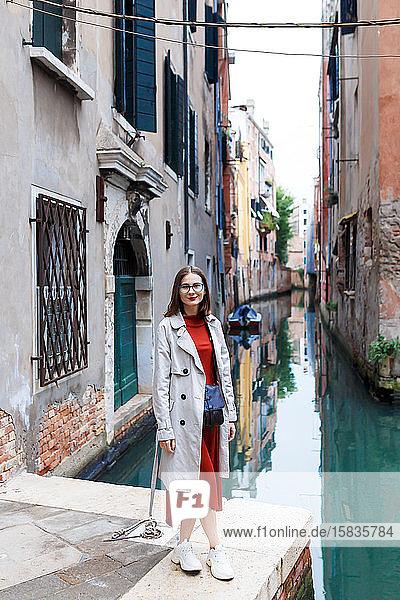 junger Tourist in Kleid und Mantel auf den Straßen von Venedig
