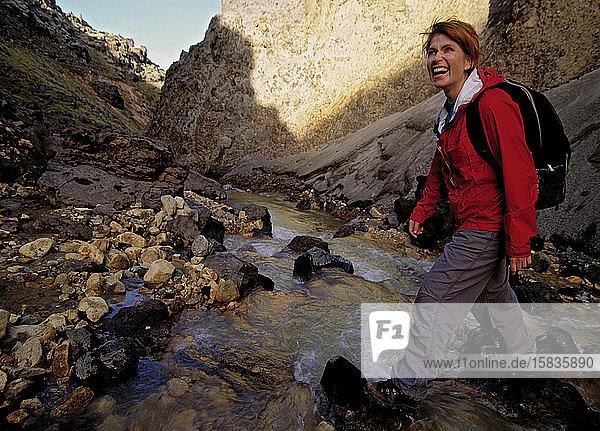 reife Frau überquert Bach in Landmannalaugar