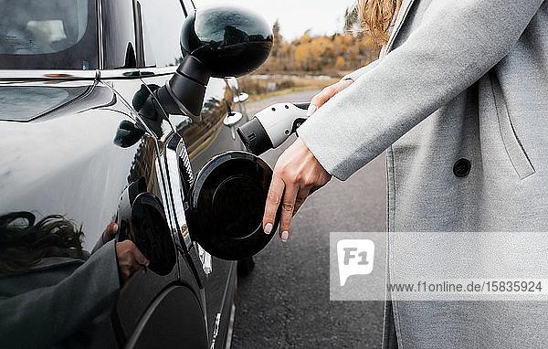 die Hand einer Frau  die ein Ladekabel an ihr Elektroauto anschließt