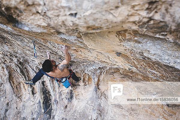 Ein Bergsteiger ohne Hemd schickt eine Sportkletterroute am spanischen Fels.