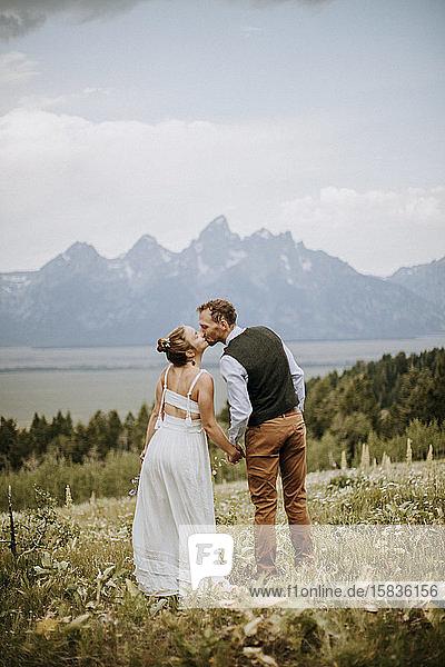 Braut und Bräutigam küssen sich in der Natur vor den Bergen  Wyoming