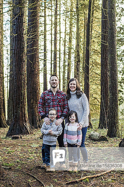 Porträt einer attraktiven Familie  die im Wald steht.