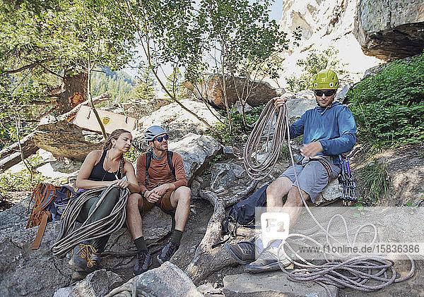 drei Personen bereiten Kletterausrüstung unter der Klippe in Wyoming vor