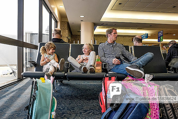 two girls and father sitting in airport terminal waiting laughing