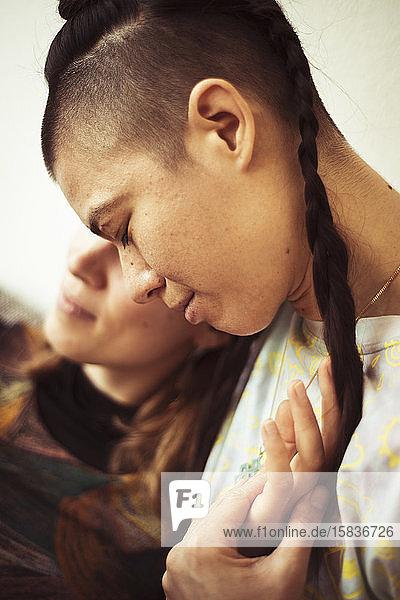 Gleichgeschlechtliche lesbische Paare bleiben zu Hause und kuscheln bei warmem Licht