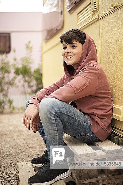 Porträt eines jungen Teenagers  der vor einem Wohnmobil sitzt und in die Kamera schaut