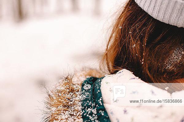 Rückansicht eines Mädchens mit Schnee auf der Fellkapuze und den Haaren