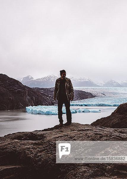 Mann steht lächelnd auf Felsen am See mit Gletschern