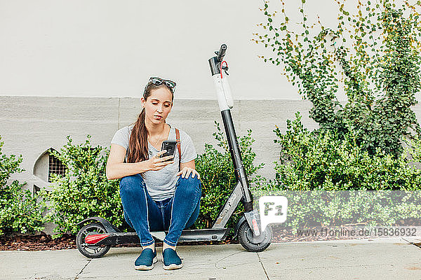 Woman Looks at Phone on Scooter
