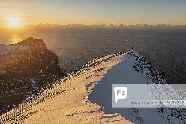 Wanderin steht allein auf schneebedecktem Berggipfel mit der Sonne im Hintergrund  Flakstadøy  Lofoten  Norwegen