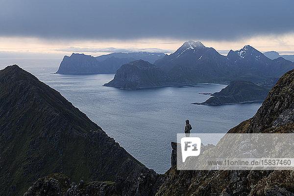Wanderin überblickt Berglandschaft von Middagstind aus  Flakstadøy  Lofoten-Inseln  Norwegen