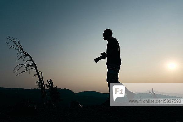 Silhouette eines Mannes mit Kamera bei Sonnenuntergang