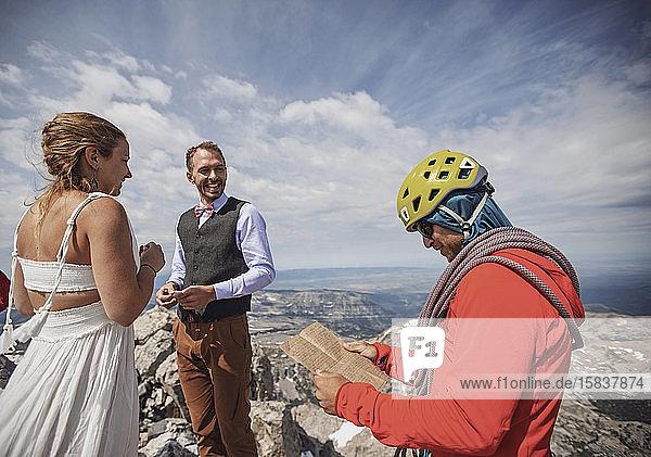 Kletterführer mit Helm liest Gelübde während der Hochzeit auf dem Berggipfel