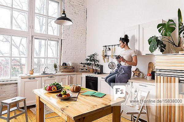 Junge und schöne Hausfrau  die in einer weißen Küche kocht