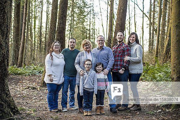 Porträt einer glücklichen achtköpfigen Familie im Wald.