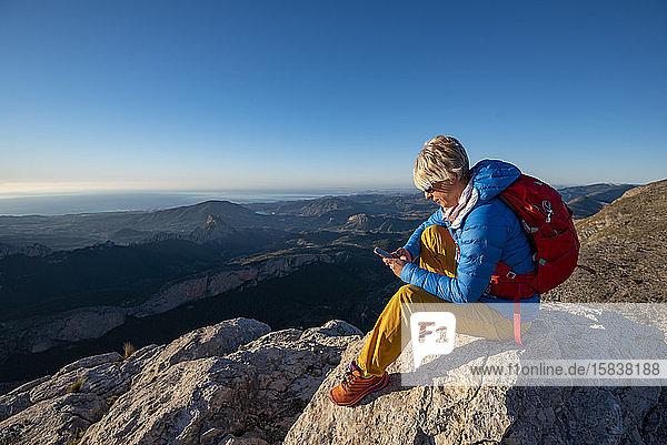 Junge Frau  die auf Felsen auf einem Berggipfel mit einem Mobiltelefon steht.
