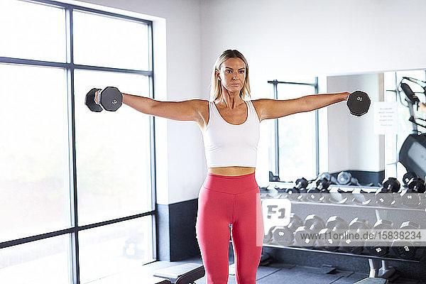 Eine Frau  die in der Turnhalle mit Gewichten trainiert.