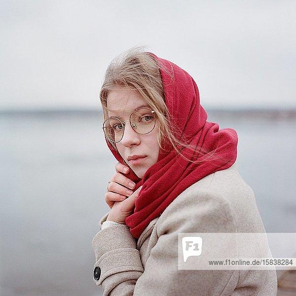Eine Frau steht mit einem roten Schal am Flussufer