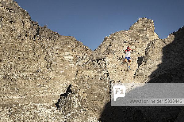 Ein Mann steigt auf einem sandigen und steilen Gelände in einem alten Bergbaugebiet ab