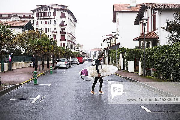 Frau surft an einem stürmischen Tag in Hendaye Plage an der Grenze zu Frankreich
