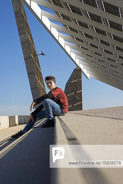 Junger Teenager sitzt auf einer Treppe im Freien und schaut bei Sonnenschein in die Kamera