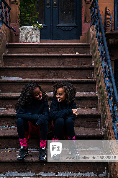 Smiling sisters in sports clothing talking while sitting on steps