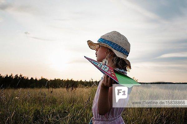Profil eines Mädchens  das bei Sonnenuntergang auf einer Wiese mit Papierflugzeugen spielt