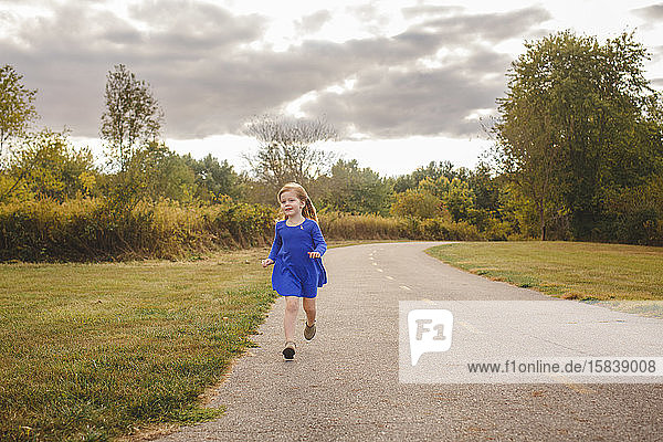Ein fröhliches kleines Mädchen in einem leuchtend blauen Kleid rennt einen Pfad in einem Park entlang