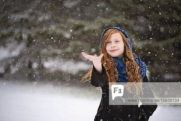 Young Red Haired Girl Playing outside in the Snow