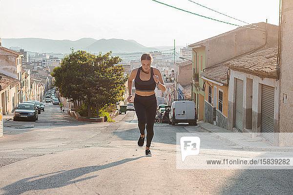 Junge Frau läuft in einer Straße einer Stadt. Weibliche Athletin  Sportkonzept