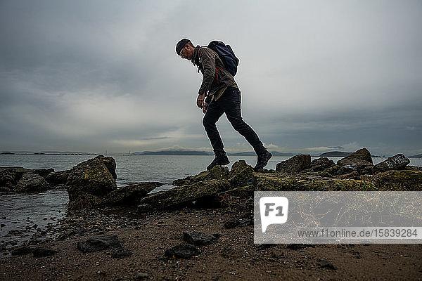 Wanderer geht über moosbewachsene Schlammsteine vom Bauwerk am Strand der Bucht